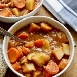 hearty vegan stew in a white bowl with a spoon