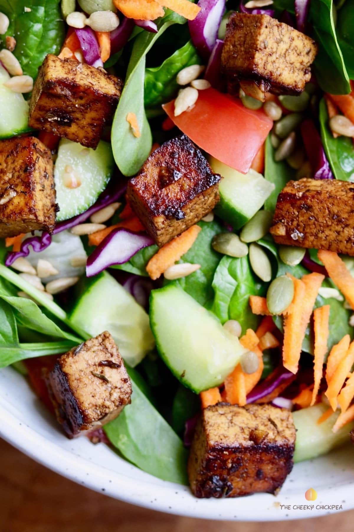 marinated tofu pieces on top of a green salad