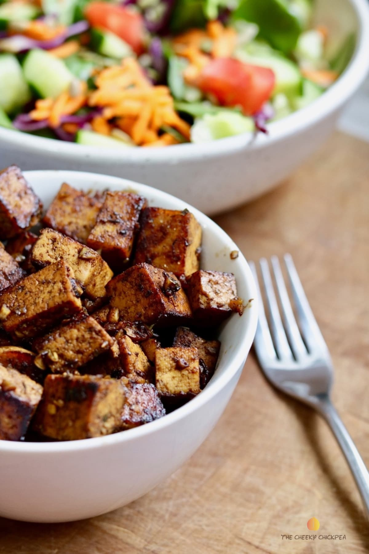 marinated tofu pieces in a white bowl beside a fork