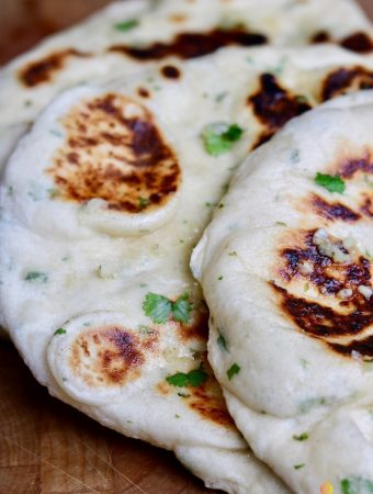 close up of two vegan naan breads on a wooden cutting board