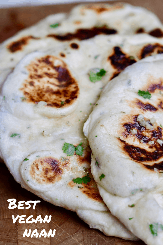 close up of two vegan naan breads on wooden cutting board