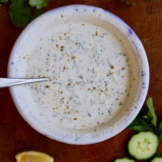 vegan raita in a white bowl on a wooden cutting board
