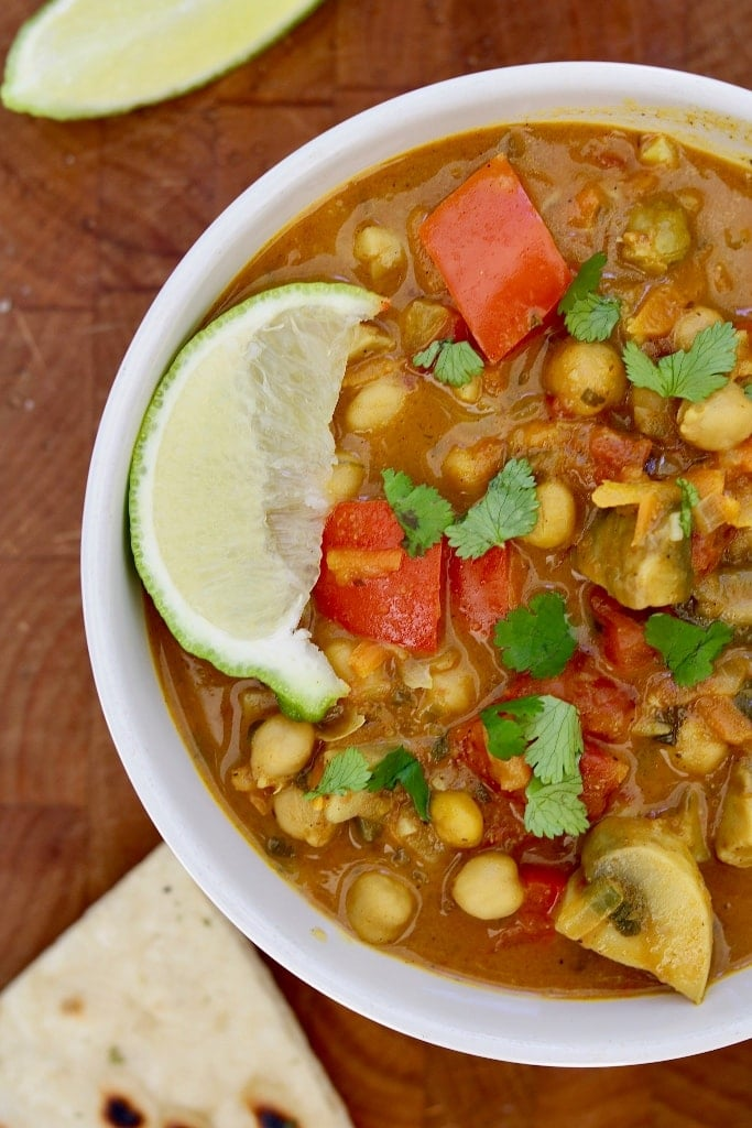 vegetable chickpea curry in a white bowl on a wooden cutting board