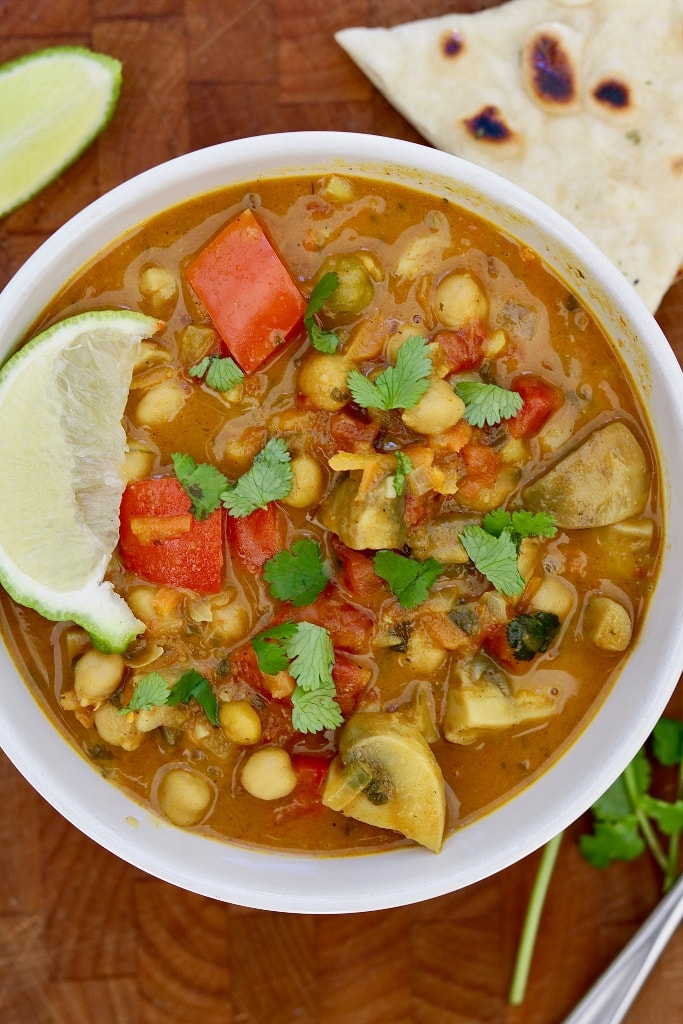vegetable chickpea curry in a white bowl with lime slice