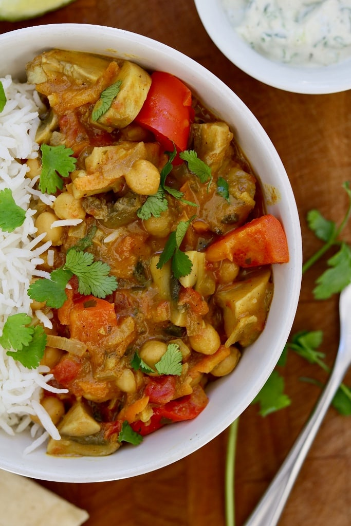 vegetable chickpea curry in a white bowl with rice