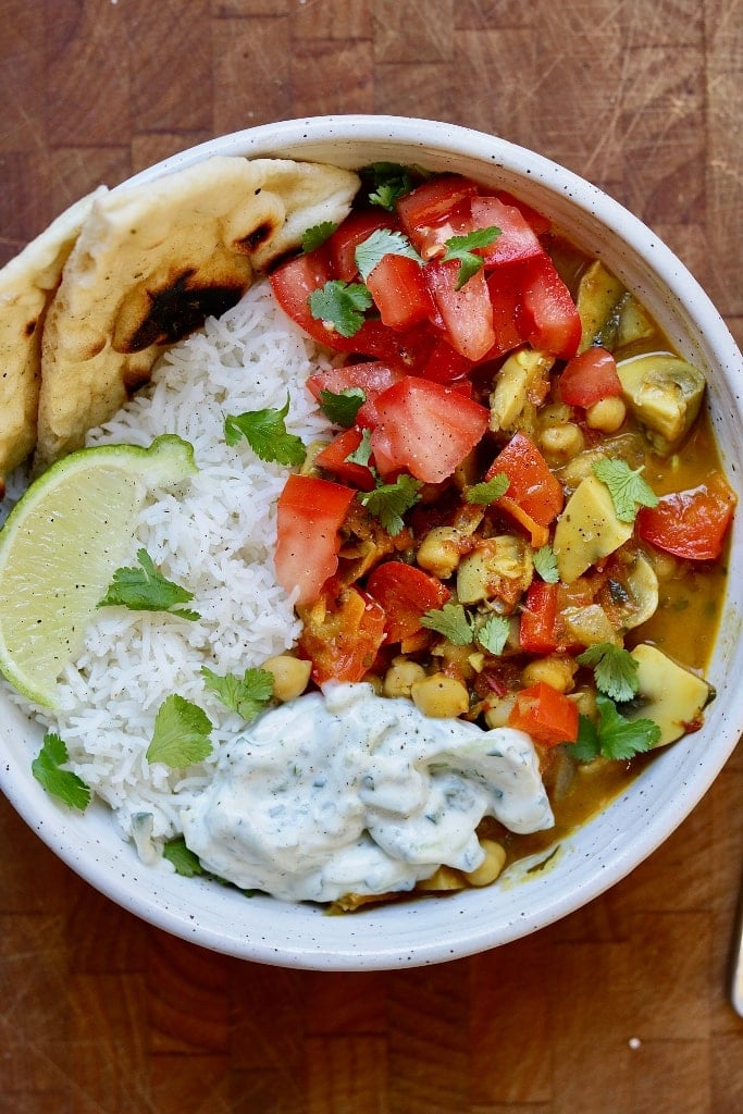 vegetable chickpea curry in a white bowl with rice naan and raita