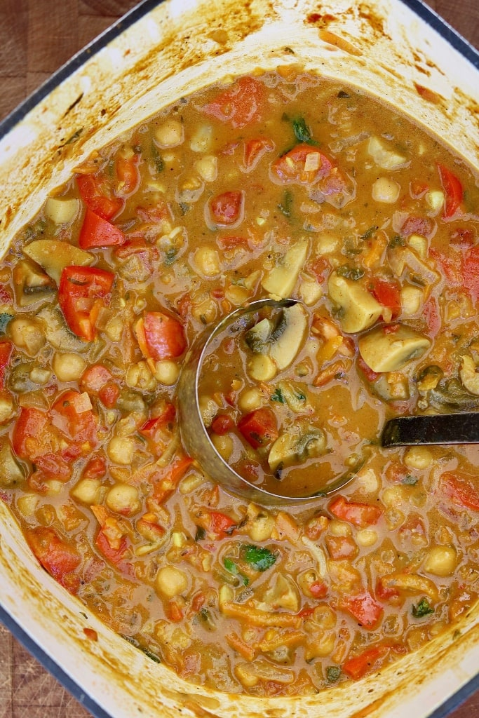 vegetable chickpea curry in a pot with a ladle