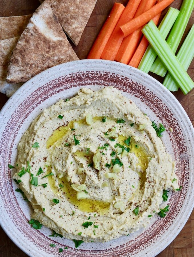 hummus in a bowl along side pita and vegetables