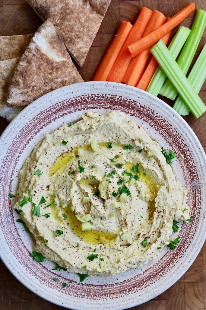 homemade hummus in a bowl along side pita and vegetables