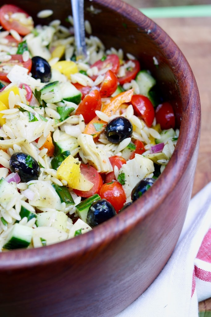 close up of mediterranean orzo salad in a wooden bowl
