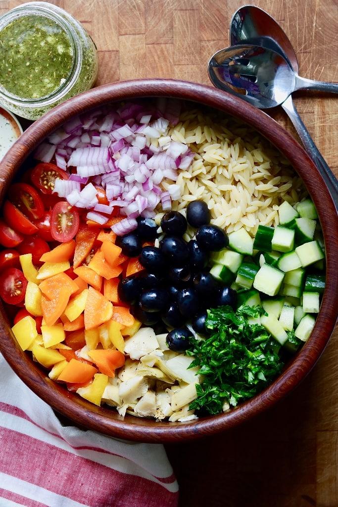 Mediterranean Orzo Salad ingredients in a wooden bowl