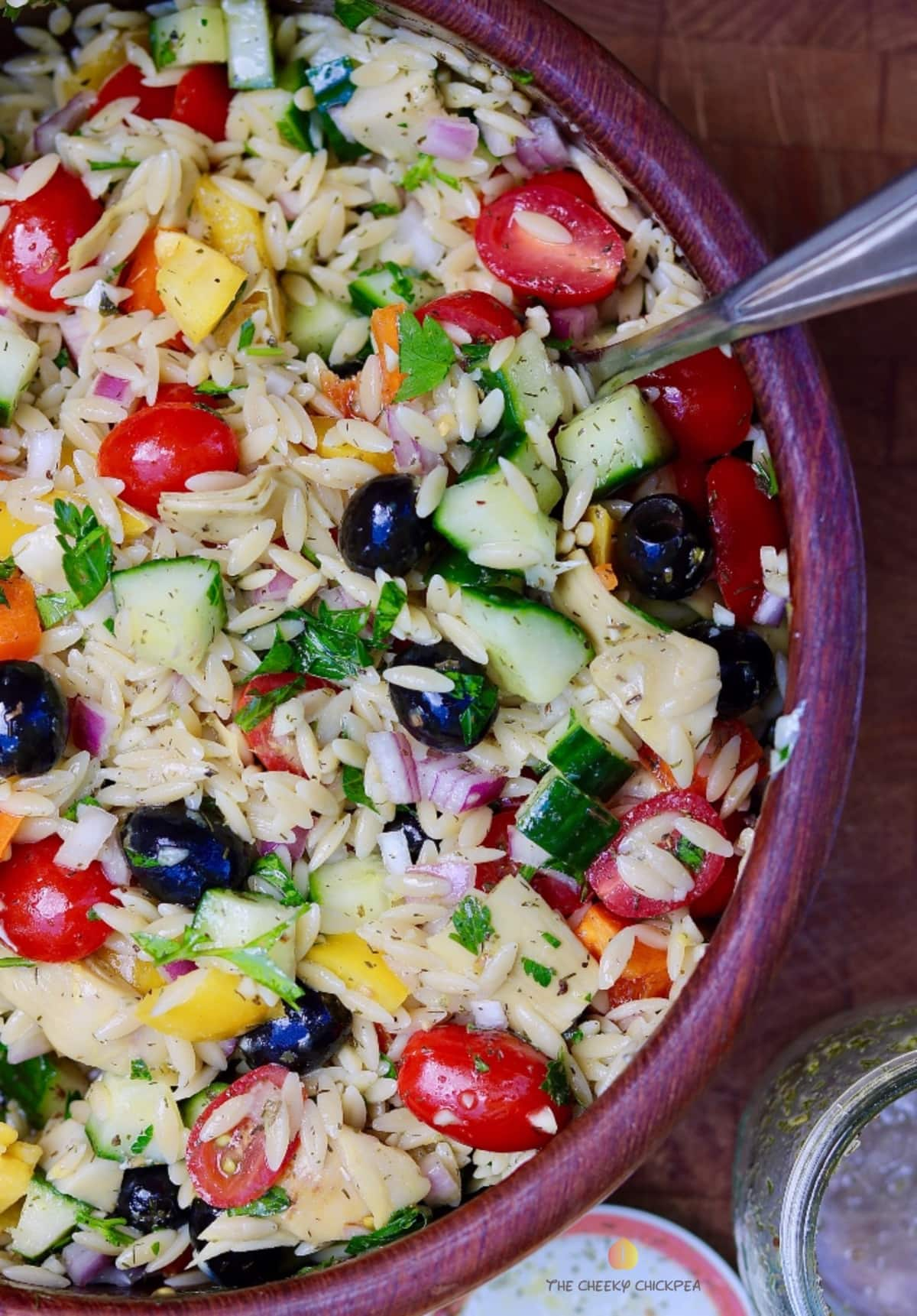 mediterranean orzo salad mixed in a wooden bowl