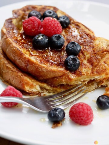 vegan French toast on a white plate with mixed berries and a fork