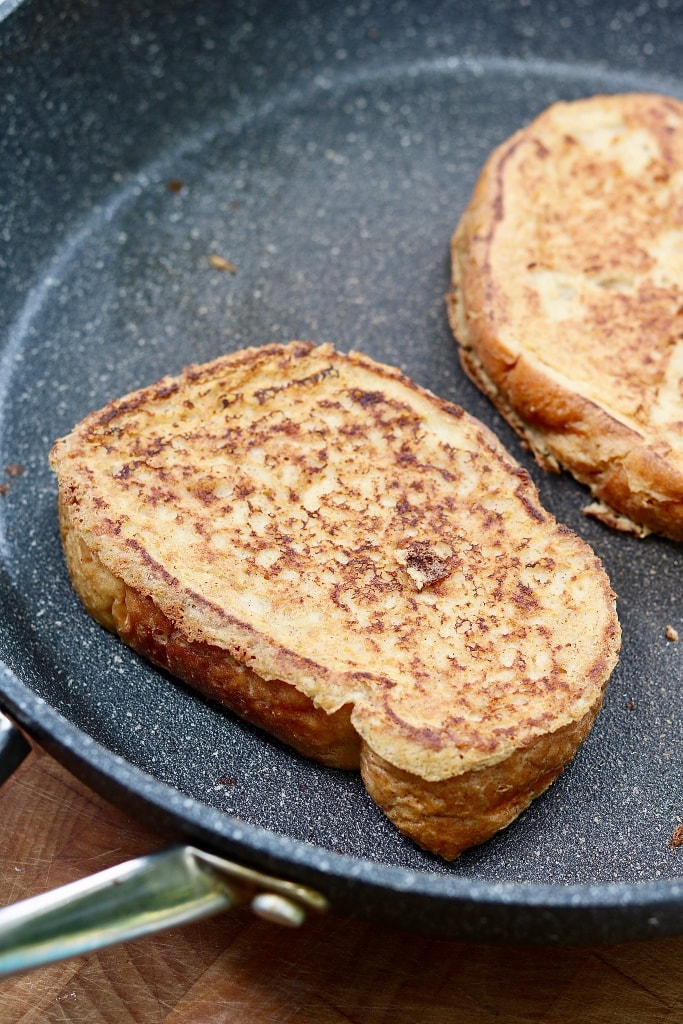 two pieces of vegan French toast fried in a pan