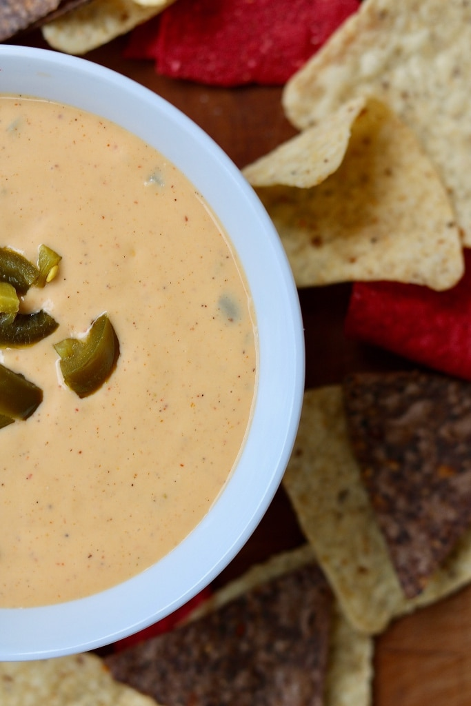 vegan nacho cheese sauce in a white bowl surrounded by tortilla chips