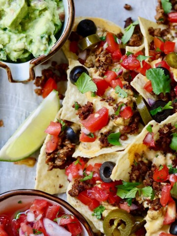 vegan nachos on a baking tray with pico de Gallo and guacamole