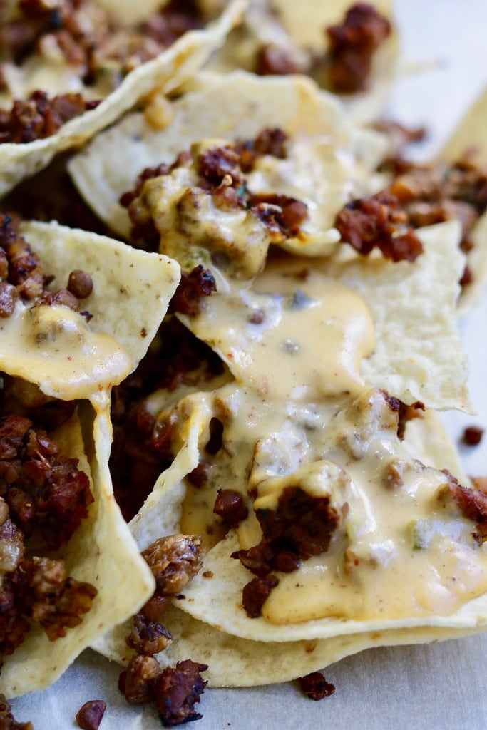 vegan taco meat on tortilla chips with nacho cheese sauce