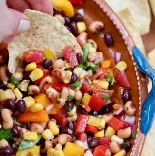 tortilla chip being dipped in cowboy caviar