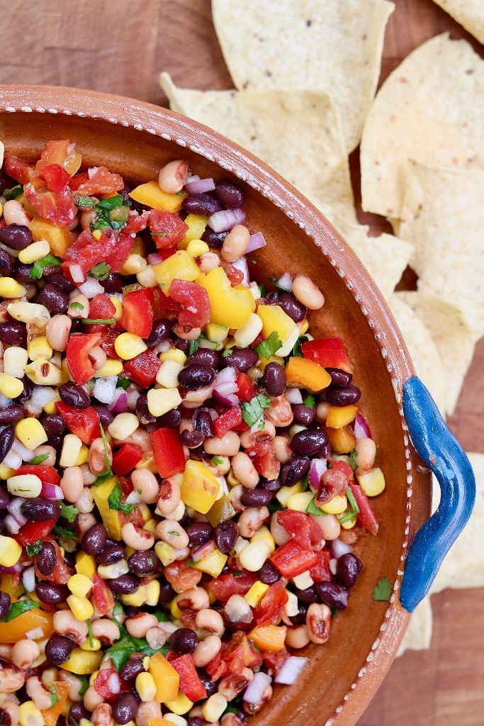 cowboy caviar in a brown bowl surrounded by tortilla chips