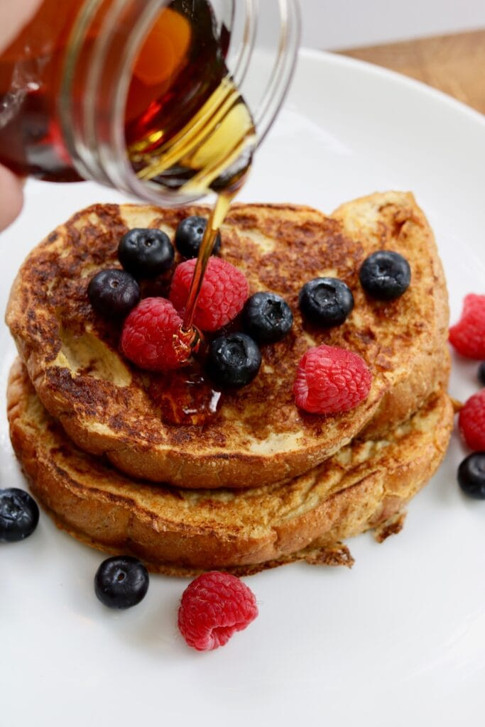maple syrup being poured over french toast with berries