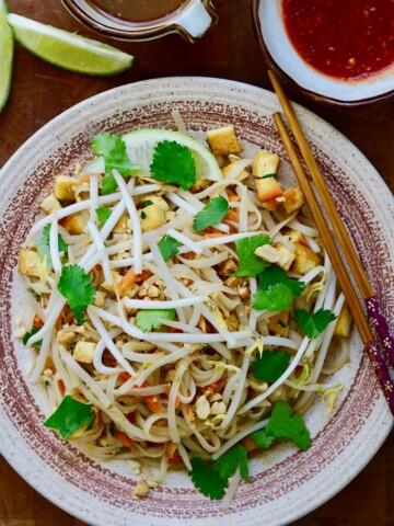 vegan pad thai on a plate beside a bowl of tamarind sauce
