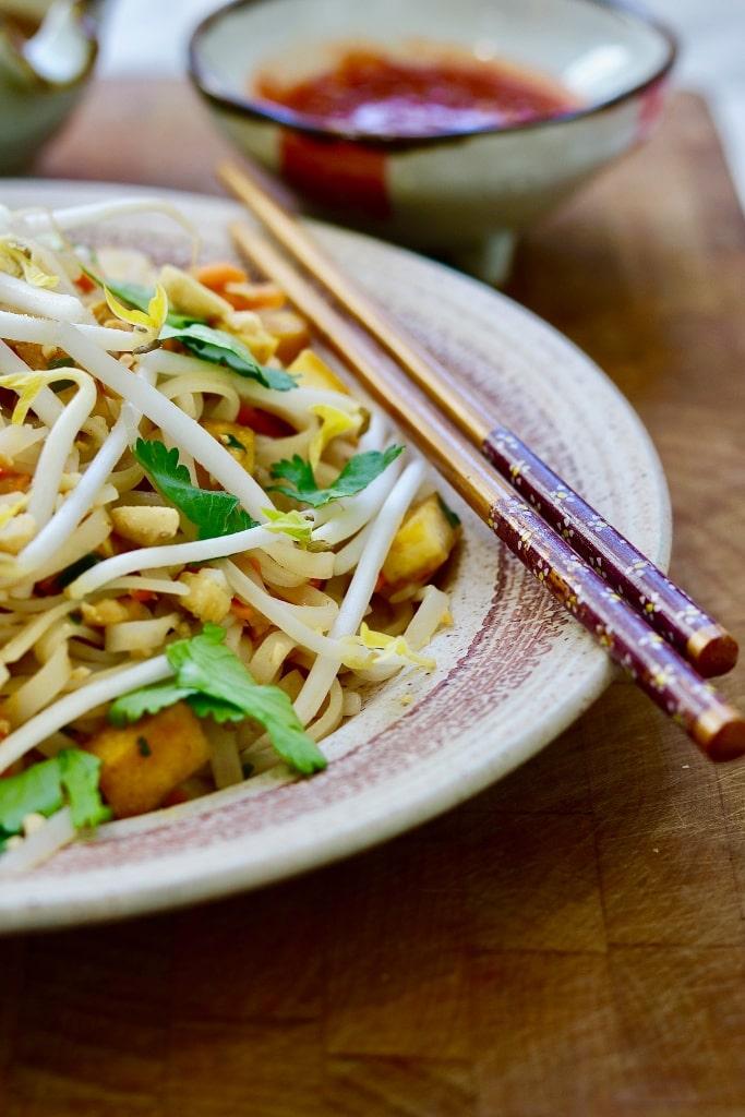 vegan pad thai on a plate with chopsticks