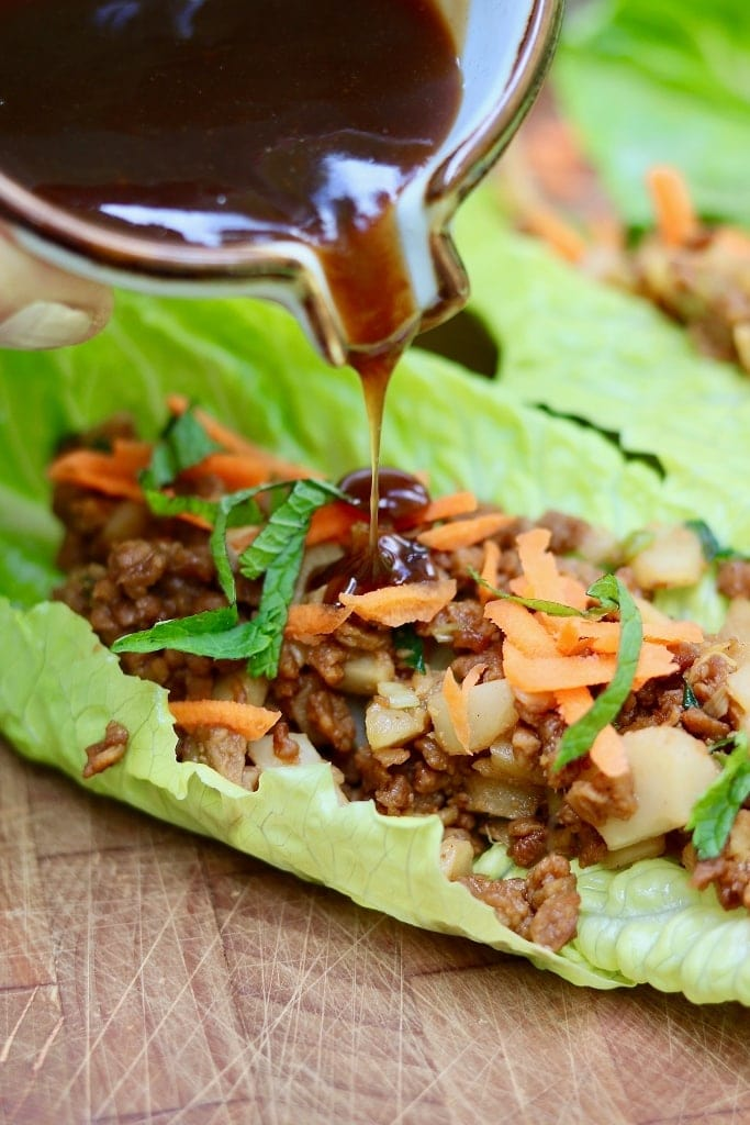 plum sauce being poured on vegetarian lettuce wrap