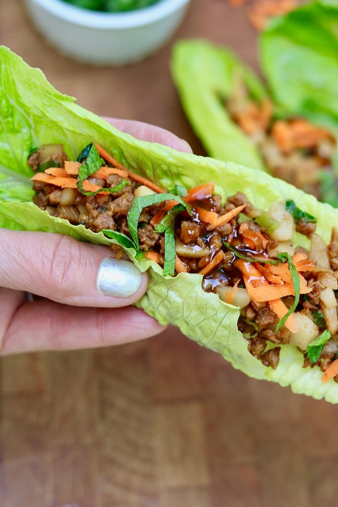 vegetarian lettuce wrap being held in the air