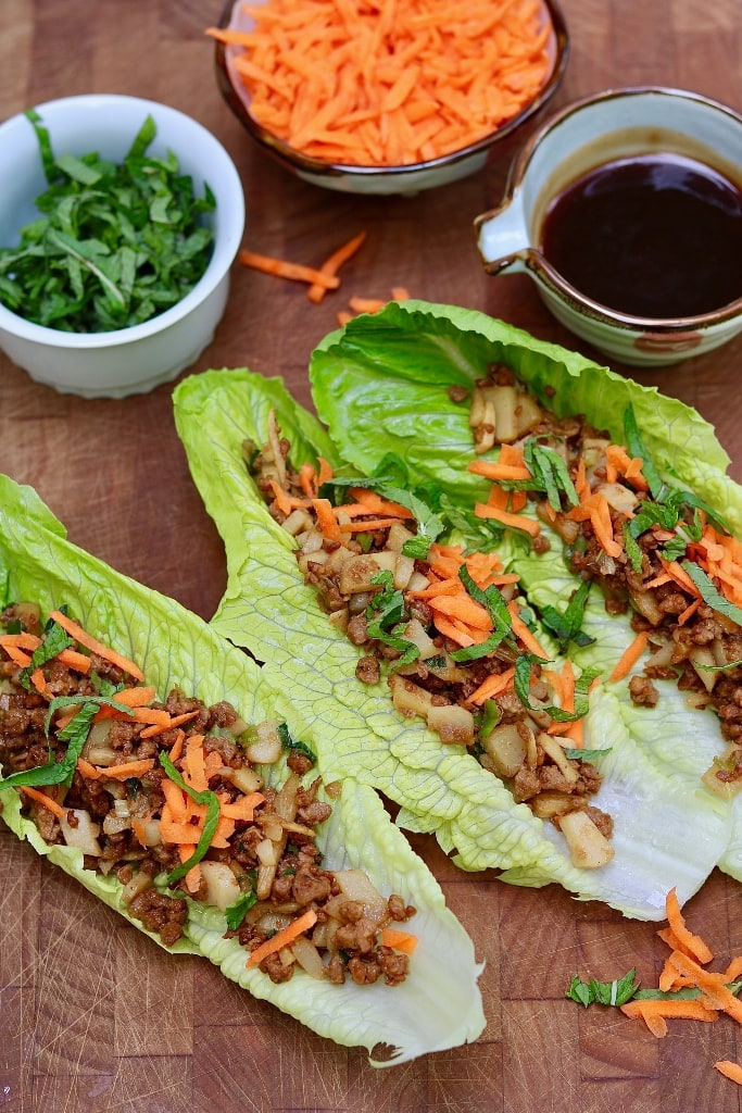 vegetarian lettuce wraps on a wooden cutting board with garnishes and plum dipping sauce