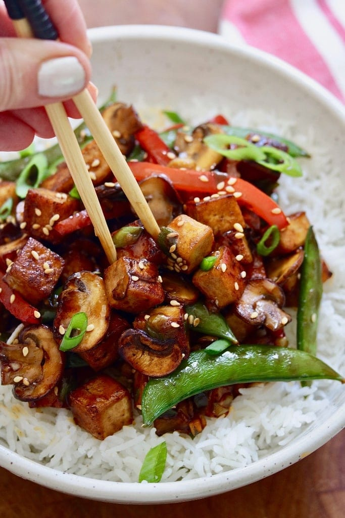 tofu stir fry in a white bowl with rice