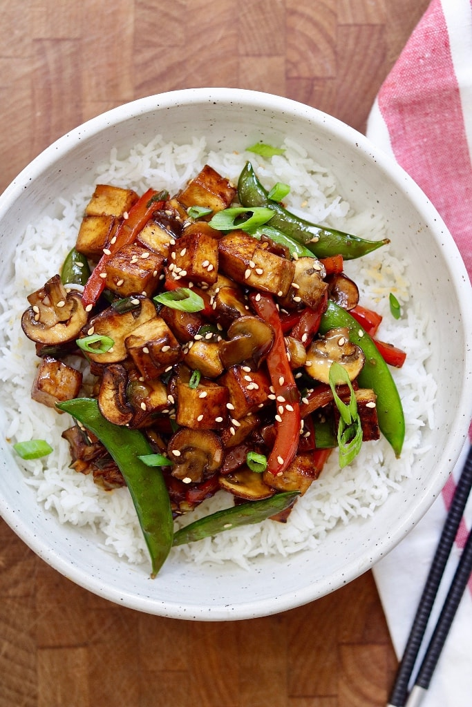 tofu stir fry served over rice in a white bowl