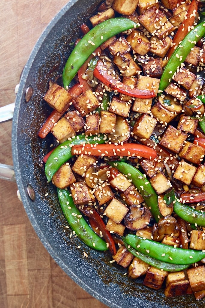 tofu stir fry in a skillet garnished with sesame seeds