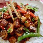 tofu stir fry in a white bowl with chopsticks
