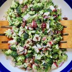 vegan broccoli salad in a white and blue bowl with wooden tongs