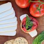 vegan mozzarella sliced on a wooden cutting board with tomatoes and crackers
