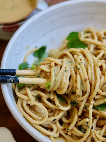 peanut noodles in a white bowl with chopsticks