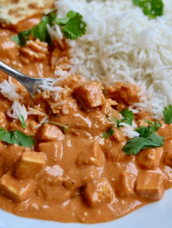 vegan butter chicken on a white plate with rice and a fork
