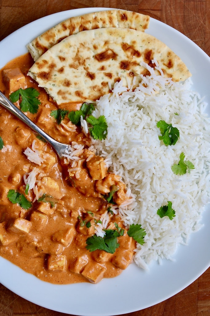 vegan butter chicken with rice naan bread and cilantro on a white plate