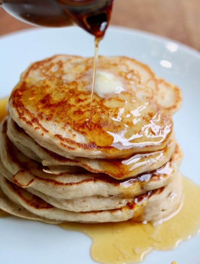 syrup being poured on vegan buttermilk pancakes stacked on a white plate
