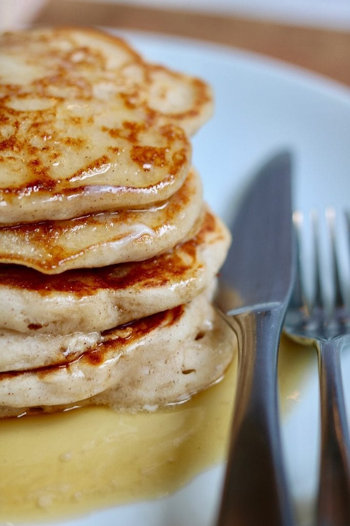 vegan buttermilk pancakes stacked on a white plate with syrup