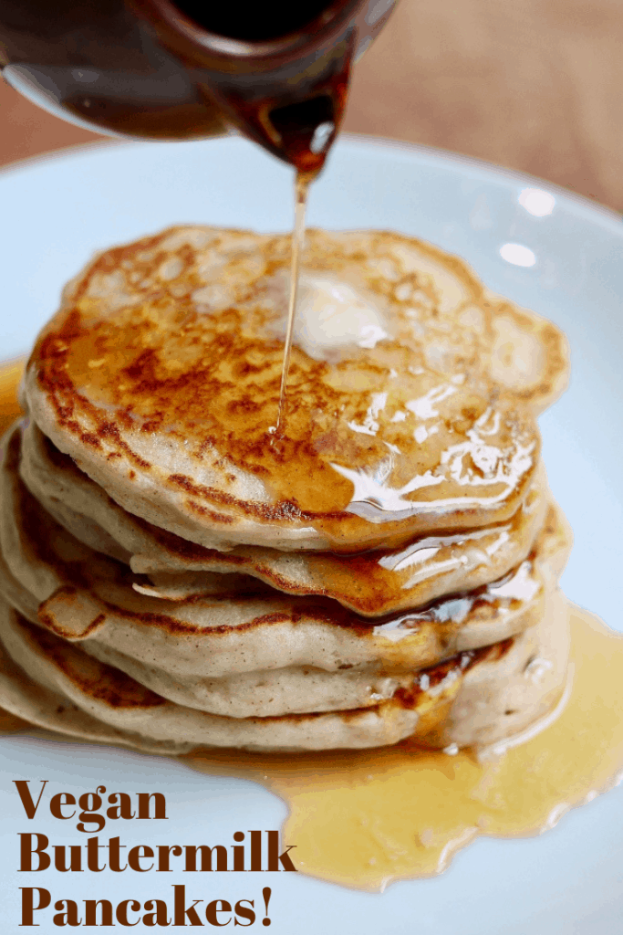 vegan pancakes stacked on a plate with syrup and butter