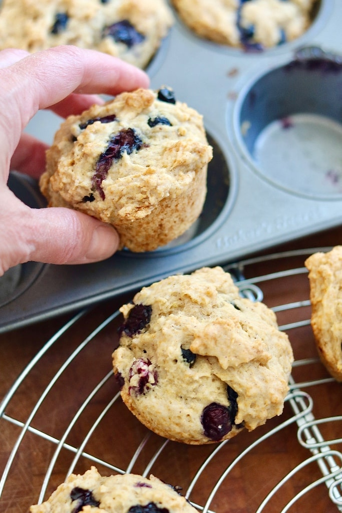 vegan blueberry muffins being placed on a cooling rack