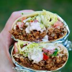 vegan burrito being held in the air