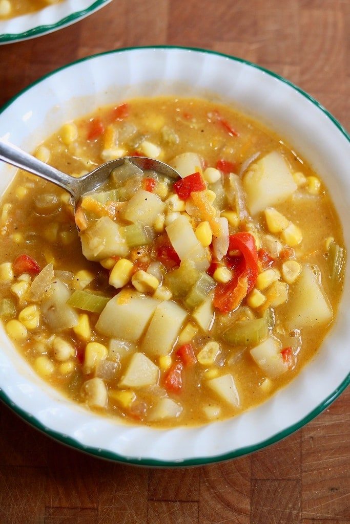 vegan corn chowder in a white bowl with a spoon