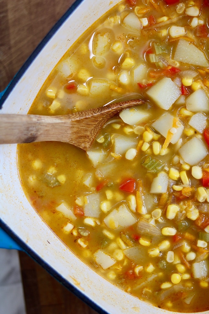 vegan corn chowder in a pot with a wooden spoon