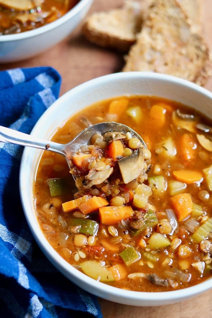 vegan italian lentil soup in a white bowl with a spoon