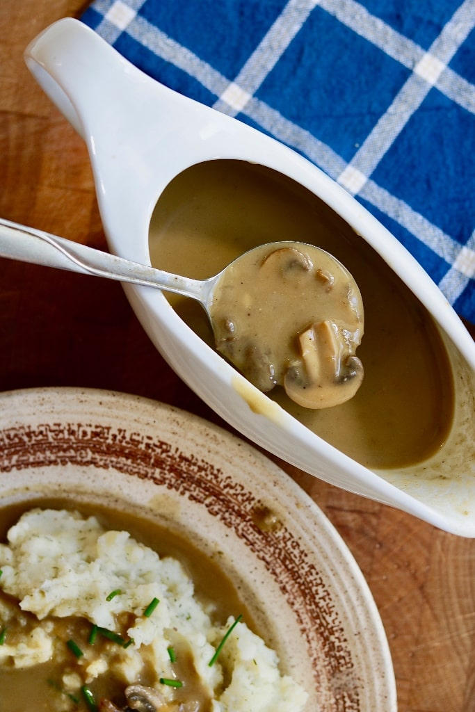 mushroom gravy in a gravy boat with a spoon