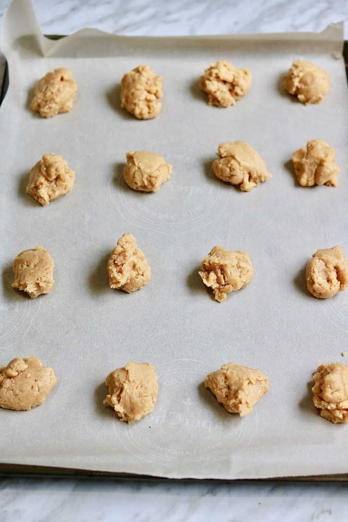 spoonfuls of peanut butter cookie dough on baking sheet
