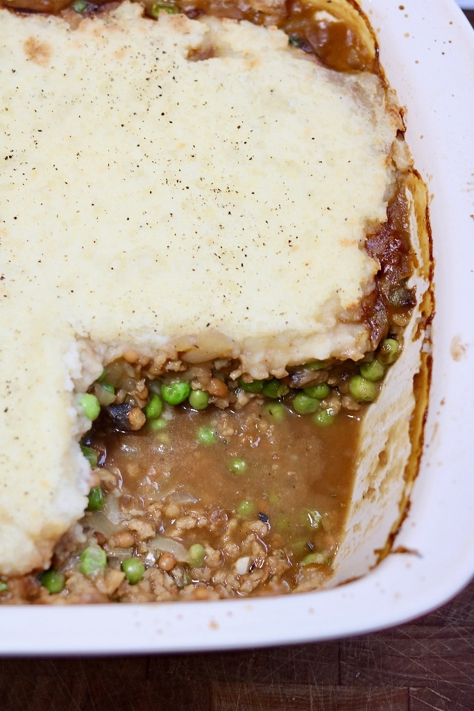 vegan shepherd's pie in casserole dish with piece missing