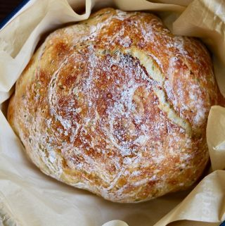 loaf of no knead bread in parchment in dutch oven